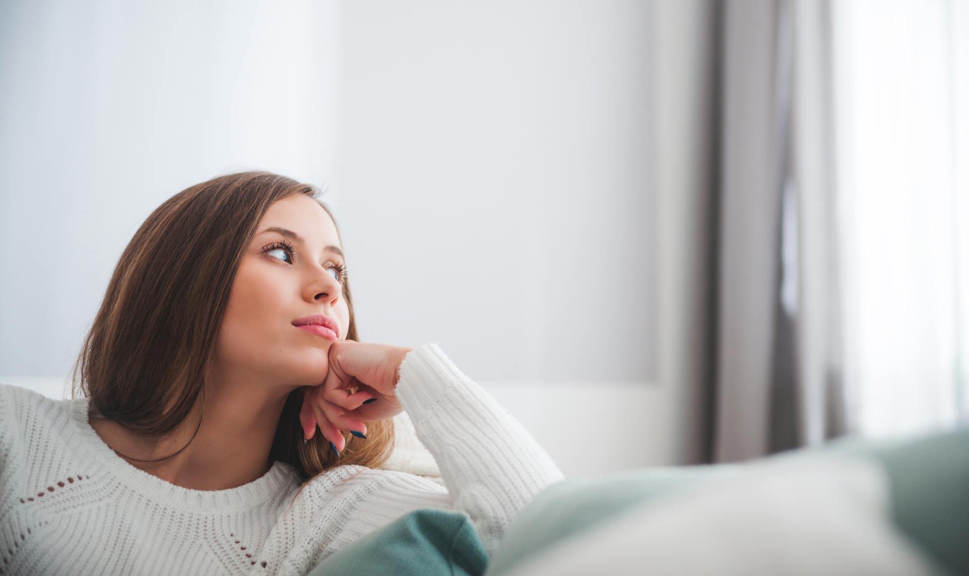 Devojka u belom džemperu sedi na krevetu i razmišlja o OTP životnom osiguranju