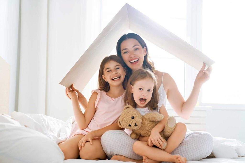 Mom and two daughters insured in OTP Insurance hold the roof symbol